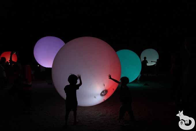 子どもが光の球体で遊んでいる様子